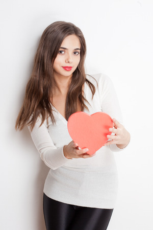 Cute young brunette beauty holding heart shaped box