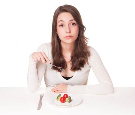 Portrait of a beautiful young brunette woman in diet dilemma.