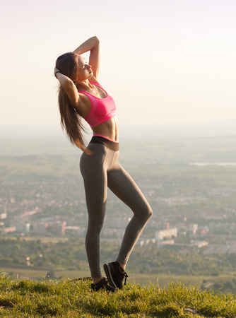 Portrait of a gorgeous young brunette woman exercising in nature.