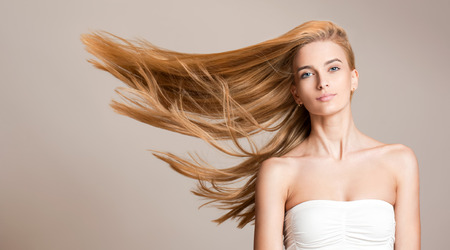 Portrait of a beautiful young blond woman with amazing flowing hair.の写真素材