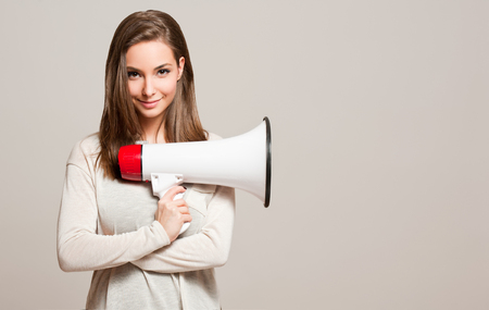 Photo pour Portrait of a gorgeous young brunette woman holding megaphone. - image libre de droit
