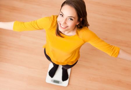 Foto de Portrait of a gorgeous young brunette woman standing on a scale. - Imagen libre de derechos