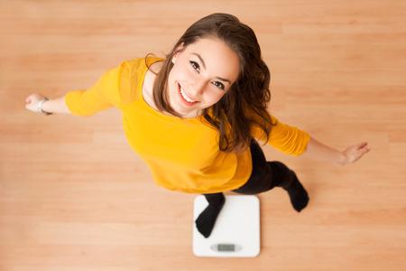Photo pour Portrait of young brunette beauty using household scale. - image libre de droit