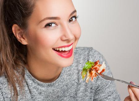 Photo pour Beautiful young brunette woman eating Italian meal. - image libre de droit
