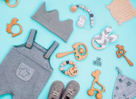 Photo pour Baby clothes and wooden toys on light blue background - image libre de droit