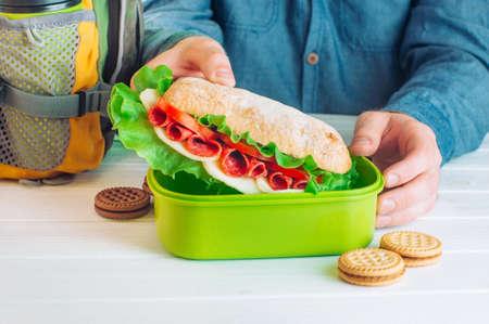 Foto für Males hands getting out sandwich from his lunch box on white wooden background selective focus - Lizenzfreies Bild