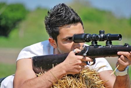 young teenager holding a gun aiming at a target