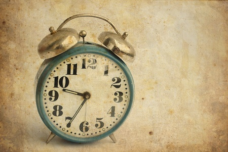 old and rusty alarm clock isolated on vintage background