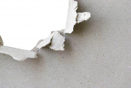 torn hole in sheet of paper with white background and copyspace