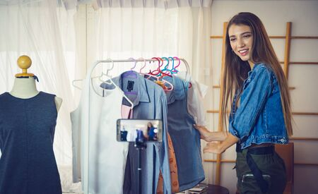 Photo pour Young girl selling clothes online by live streaming from mobile phone. - image libre de droit