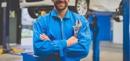 Photo pour Mechanics holding wrench in the workshop garage. Auto car services concepts - image libre de droit