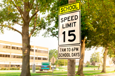 Photo for Sign indicating school zone speed limit of 15 miles per hour with school building seen in the background - Royalty Free Image