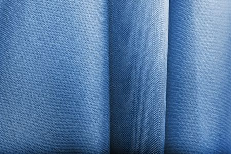 Abstract blue textile texture with selective focus on creases
