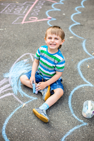 Cute boy and girl drawing with chalk on the sidewalk in the park. Summer activities for children. Creative drawing of a child with blue chalk on the road.