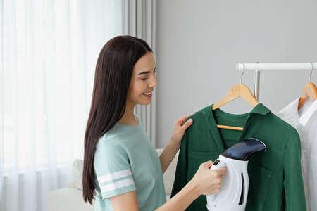 Photo pour Woman steaming shirt on hanger at home - image libre de droit