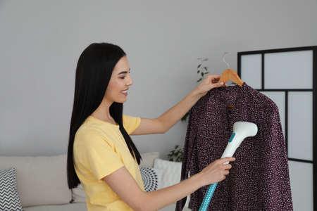 Photo pour Woman steaming blouse on hanger at home - image libre de droit