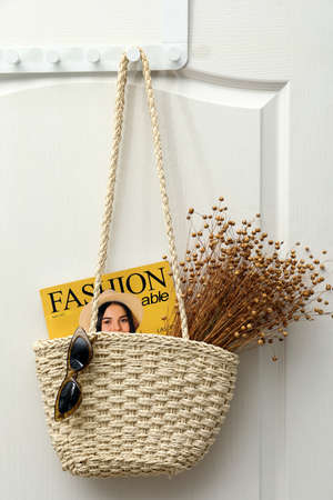Photo pour Stylish beach bag with beautiful dried flowers, sunglasses and magazine hanging on white wooden door - image libre de droit