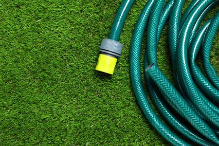 Photo pour Watering hose on green grass, top view. Space for text - image libre de droit