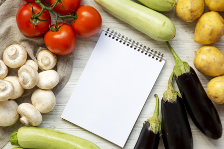 Set of different raw veggies for cooking health vegetable food, blank notebook on a white wooden background, top view. Overhead, flat lay.