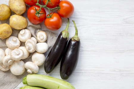 Set of raw veggies for cooking health vegetable food on a white wooden table, top view. Overhead, flat lay. Copy space.