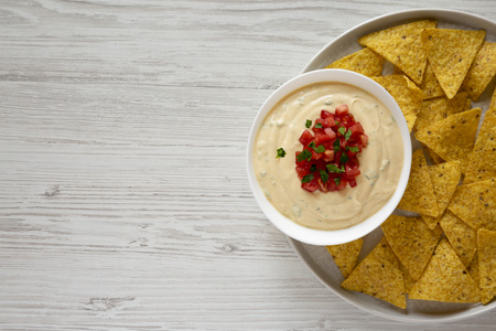 Homemade cheesy dip in a bowl, yellow tortilla chips, top view. Flat lay, overhead, from above. Close-up.