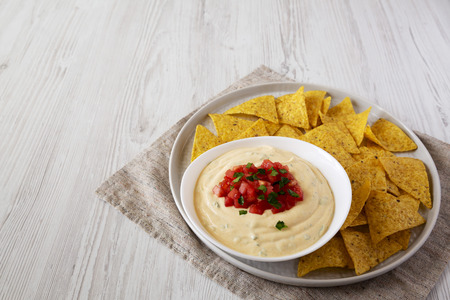 Foto de Homemade cheesy dip in a bowl, yellow tortilla chips, side view. Space for text. - Imagen libre de derechos