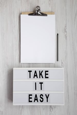 Photo pour 'Take it easy' words on a lightbox, clipboard with blank sheet of paper on a white wooden background, overhead view. Top view, from above, flat lay. Copy space. - image libre de droit