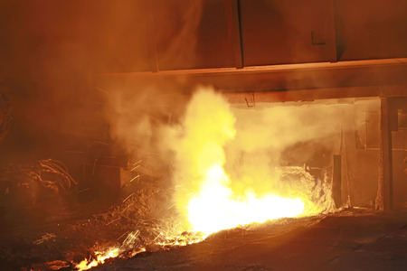 hot molten iron flowing from blast furnace, closeup of photo