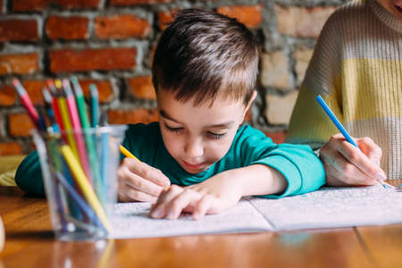 Photo pour Portrait of a cute happy preschool boy at home or in a cafe draws. - image libre de droit