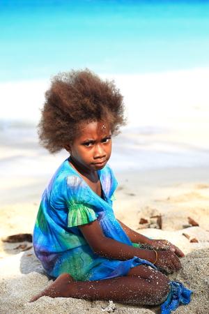 ESPIRITU SANTO,VANUATU-OCTOBER 19, 2014:  Ni-vanuatu girl shows the local fashion in hair cutting while playing on the beach on October 19, in Port Olry-Vanuatu.
