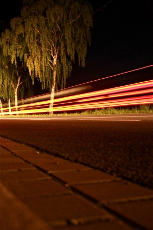 street in the night with driving cars