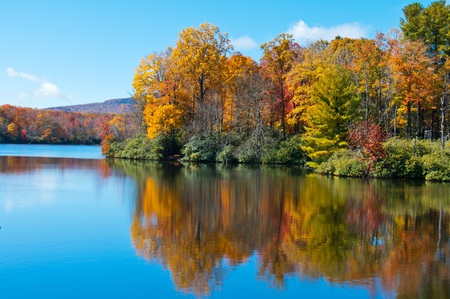 Photo pour Colorful autumn foliage casts its reflection on the calm waters of the North Carolina lake. - image libre de droit