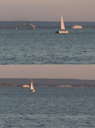 distant sailing boats on the water. vertical