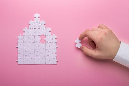 Foto de White puzzle. House shape puzzle. The concept of rent, mortgage. Hand holding piece of white puzzle. Pink background. Top view Top view. Copy space - Imagen libre de derechos