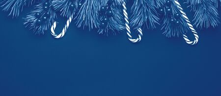 Foto de Christmas background with tree branches, candy cane and holly on black wooden background. Horizontal banner. Color of the year 2020 classic blue toned - Image - Imagen libre de derechos
