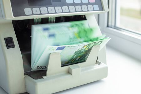 Photo pour Euro EUR banknotes of 100 on money counter machine. Automatic money counting in the machine - Image - image libre de droit