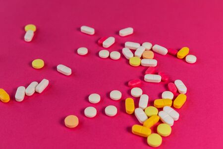 Different medicine pills, tablets on pink background. Many pills and tablets with space for text. Health care. Top view. Copy space. New image. Pharmaceutical picture. Closeup. Soft focus. Close-up