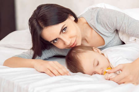 Photo pour Motherhood. Mother smiling hugging baby with dummy sleeping lying on bed close-up - image libre de droit