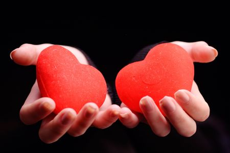 Woman holding two red hearts against black background