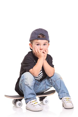 Little child sitting on a skateboard isolated on white background