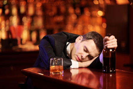 Young drunk man sleeping in the bar, with glass of whiskey in his hand