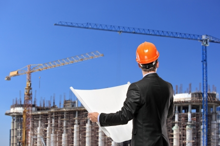 A foreman in a black suit holding a blueprints and looking towards the construction site