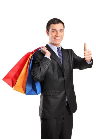 A happy male holding shopping bags and giving thumb up isolated on white background