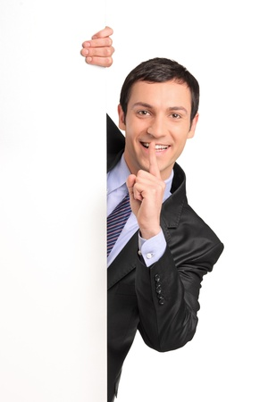 Businessman in a suit gesturing silence with his finger over his mouth, behind white panel, isolated on white background
