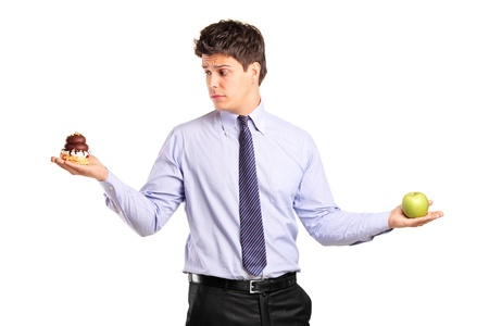A man holding an apple and slice of cake trying to decide which one to eat isolated on white background