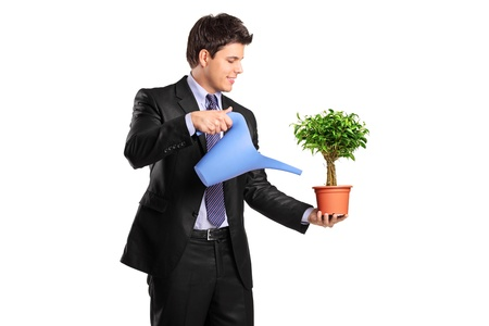 A businessman holding a watering can and flower pot isolated on white background