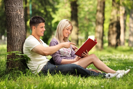 A boyfriend and girlfriend reading a book in a city park Skopje, Macedonia