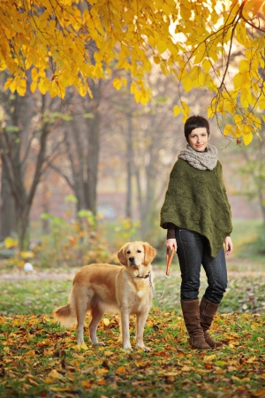 Young girl and her dog (Labrador retriever) walking in autumn in a city park Skopje, Macedonia