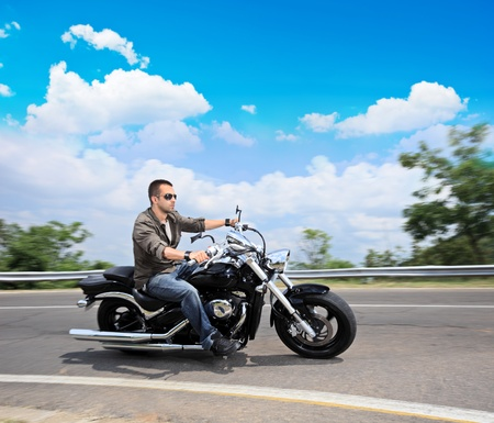 A view of a young man riding a motorcycle on an open road