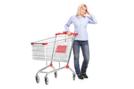 A bankrupt woman posing next to an empty shopping cart isolated on white background